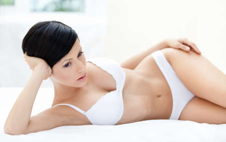 vrouw ondergoed: Vrouw in ondergoed ligt in het zachte bed, witte achtergrond
