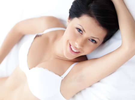 Woman in underwear is lying in the wide bed, white background photo