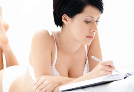 guardar silencio: Mujer en ropa interior hace que algunas notas mientras está acostado en la cama, aislado en blanco Foto de archivo