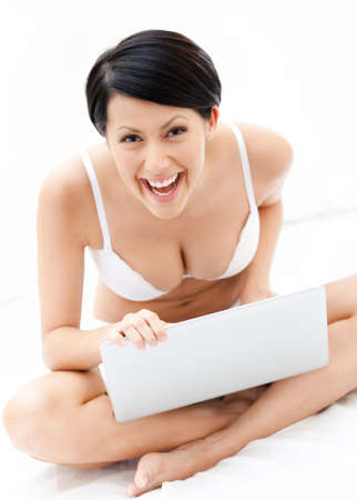 Woman in underwear is working on the thin computer while lying on the bed, isolated on white background photo