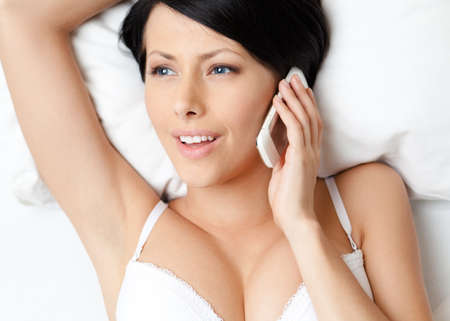 Woman in underwear speaks on telephone while lying in the bedstead, white background photo