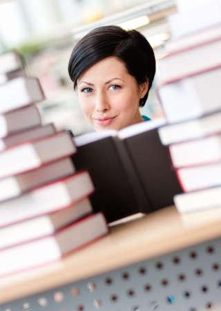 learning process: Female student sitting at the desk is surrounded with piles of books  Learning process Stock Photo