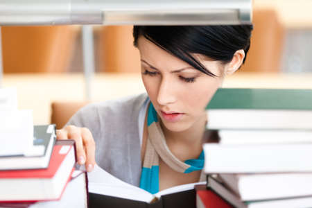 Reading book female student sitting at the desk surrounded with piles of books at the library  Information concept Stock Photo - 15647301