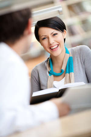 Pretty woman communicates with man showing her something in the book sitting at the desk at the library photo