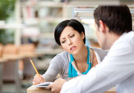 study desk: Pretty woman communicates with young man showing her something in the book sitting at the desk at the library