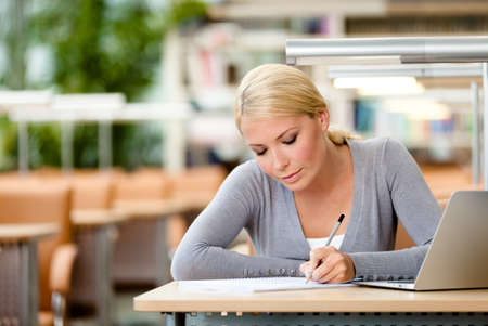 Female student working on the laptop sitting at the table  Process of learning