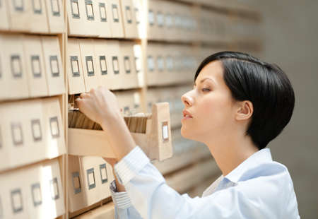 Woman searches something in card catalog composed of set of wood boxes at the library  Information photo