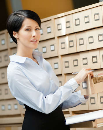 pencil skirt: Pretty woman searches something in card catalog composed of set of wood boxes at the library  Information Stock Photo