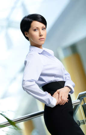 Portrait of a handsome business woman wearing white shirt and black skirt at business centre photo