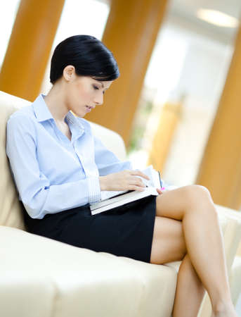 Business woman rests at the leather sofa reading book at the hall photo