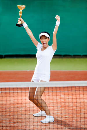 Professional female tennis player won the cup at the sport competition  Victory photo