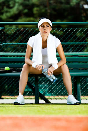 Professional female tennis player rests with bottle of water on the bench at the tennis court photo