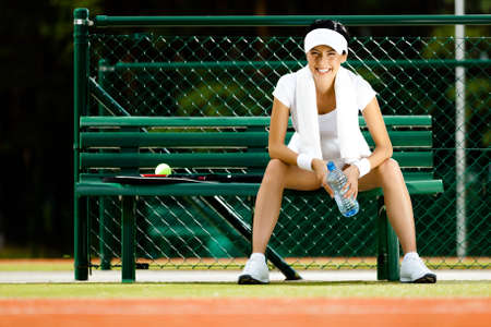 girl sit: Tennis player rests with bottle of water on the bench at the tennis court