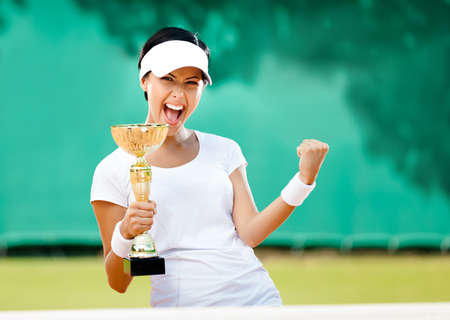 Pretty tennis player won the cup at the sport competition  Victory photo