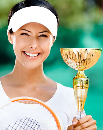 Successful female tennis player won the cup at the sport competition  Victory photo