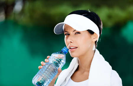 Sporty woman with bottle of water after tennis match photo