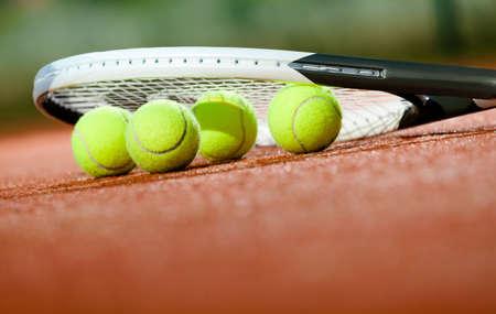 cerillas: Primer plano de una raqueta de tenis y pelotas en la cancha de tenis de arcilla