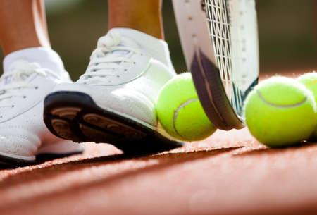 raqueta de tenis: Piernas de la muchacha atlética cerca de la raqueta de tenis y pelotas