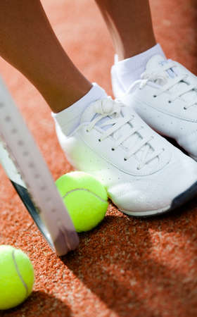 Legs of sporty girl near the tennis racket and balls photo