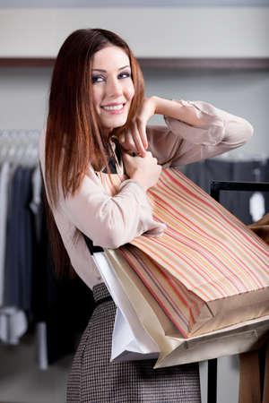 long shots: Donna che porta sacchetti di carta e si sente bene dopo lo shopping Archivio Fotografico