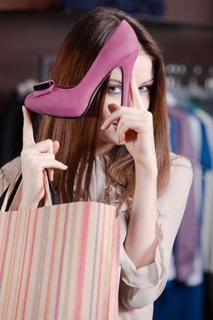 comprando zapatos: La mujer juega con zapatos fucsia excelentes en la tienda