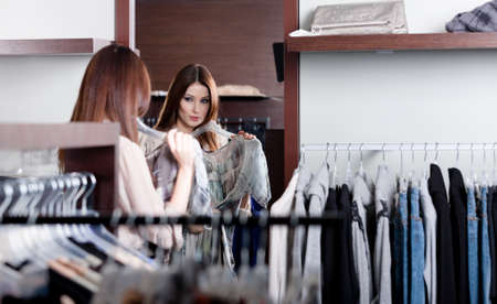 admires: Woman admires herself at the mirror in the shopping mall Stock Photo