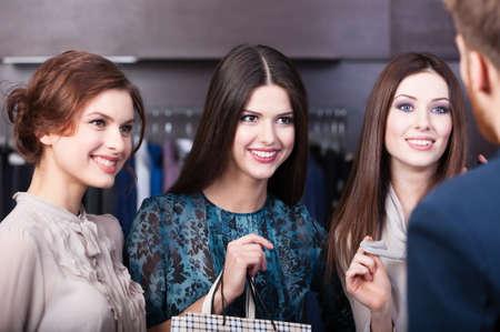 Three girlfriends talk with salesperson photo