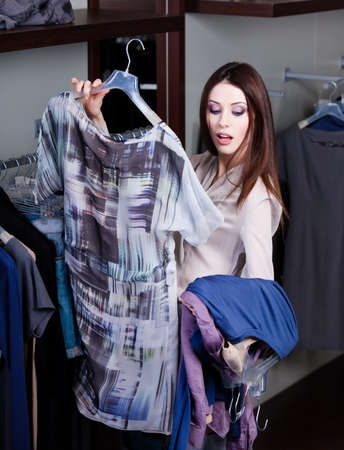 Young woman hesitates whether to try clothes on or not photo