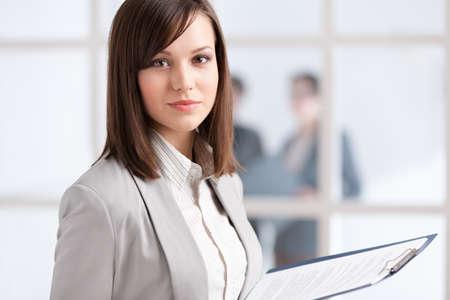 businesswoman suit: Ejecutivo con la tableta en el fondo de la pared de cristal con la gente