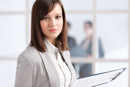 woman with document: Executive with tablet on the glass wall background with people