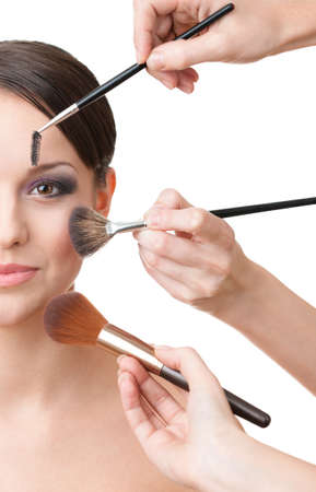 esthetician: Three hands of makeup artists applying cosmetics on the womans face, isolated on white. Half face shot Stock Photo