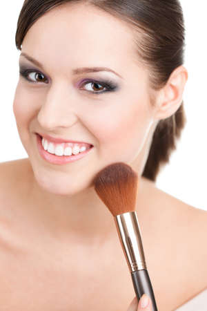 Woman applying cosmetics to her face with the help of cosmetic brush, isolated on white photo