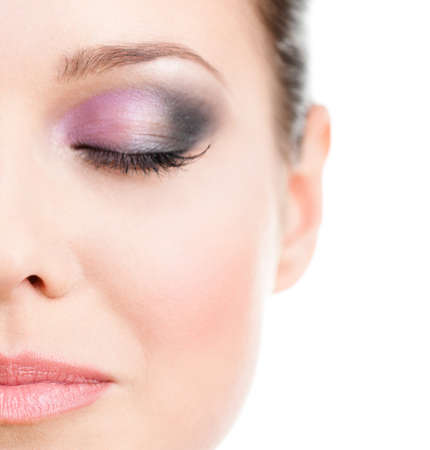 Close up of woman's half face with closed eye with makeup of pink and grey eye shades, isolated on white photo