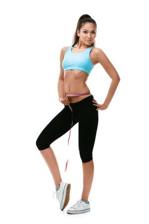 girl in sportswear: Woman measures her waist with   measuring tape, isolated on white