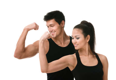 Two sportive people in black sportswear showing their biceps, isolated on white photo