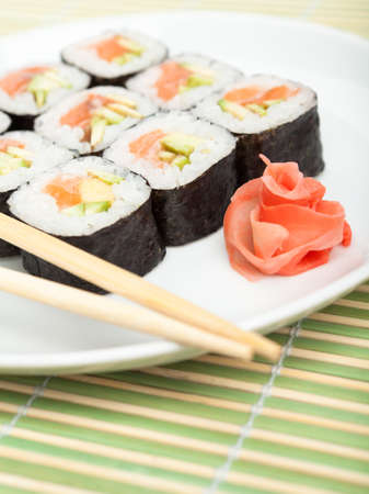 Sushi rolls on the plate with wood white chopsticks on green mat photo