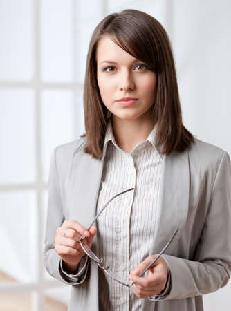 woman serious: Portrait of a handsome businesswoman handing glasses, isolated on white Stock Photo