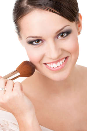 Girl applying cosmetics to her face with the help of cosmetic brush, isolated on white photo