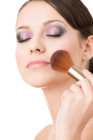 esthetician: Woman applying cosmetics to her face with eyes shut with the help of cosmetic brush, isolated on white