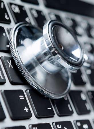 solucion de problemas: Primer plano de estetoscopio en el teclado de la computadora portátil. Healthcare concepto