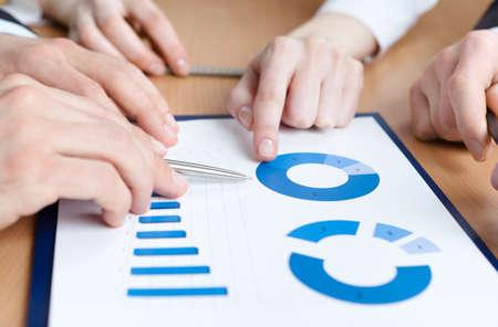 alzando la mano: Primer plano de las manos de los directivos discutiendo diagrama y se sienta a la mesa