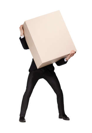carries: Manager in suit bears a huge parcel, isolated on white Stock Photo