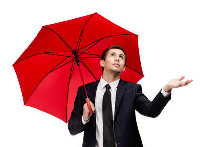 Palming up business man with opened umbrella checks the rain, isolated on white photo