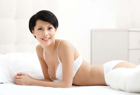 ideal: Woman with perfect body in bra is lying in the wide bed Stock Photo
