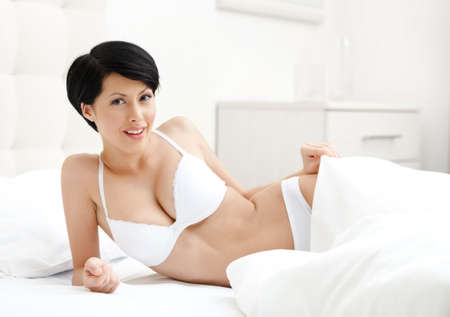 gladly: Woman in underwear is lying in the bed with white bed linen