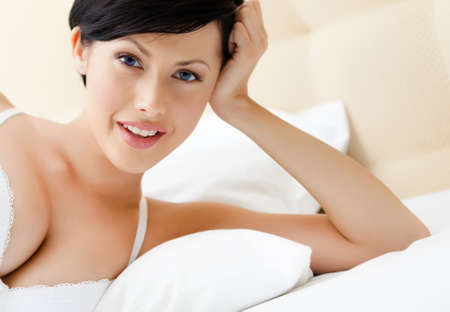 Woman in bra is lying in the spacious bed photo