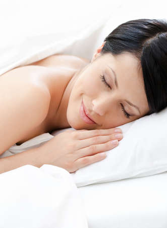Dreamy woman sleeps in bed, white background photo