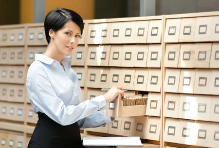 pencil skirt: Pretty woman searches something in card catalog composed of set of wood boxes at the library. Studying