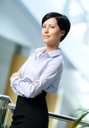 short skirt: Portrait of a handsome professional business woman wearing white shirt and black skirt at business centre