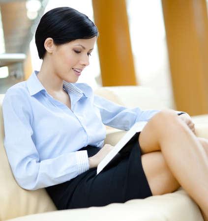 falda corta: La mujer descansa en el sofá leyendo un libro interesante en la sala de Foto de archivo